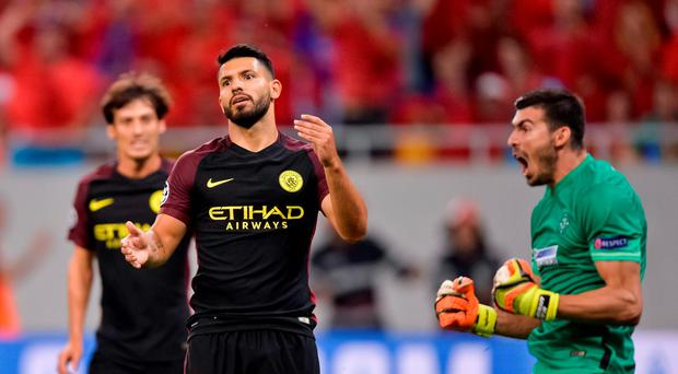 Manchester City's Sergio Aguero, center, reacts after missing a penalty
