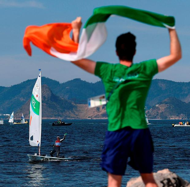 Sailing team-mate Finn Lynch waves at her from the shore. Photo by Brendan Moran/Sportsfile