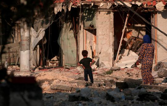 A woman walks with a boy on the rubble of damaged shops and buildings in Manbij, Aleppo Governorate, Syria, August 16, 2016
