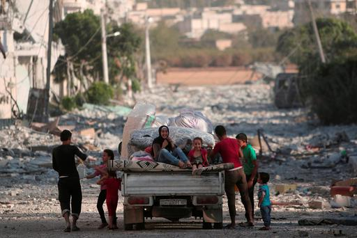 Children sit on a pick-up truck loaded with belongings along a damaged street in Manbij, Aleppo Governorate, Syria, August 16, 2016