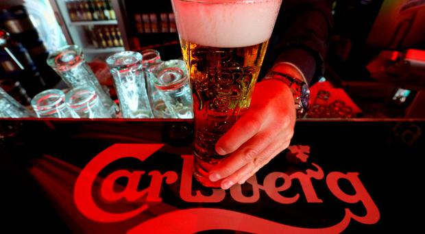 A bartender holds a glass of Carlsberg beer in a bar. REUTERS/Alexander Demianchuk/FilesGLOBAL BUSINESS WEEK AHEAD PACKAGE - SEARCH