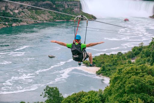 A tourist suspended above the water from zip lines makes his way at speeds of up to 40 mph toward the the mist of the Horseshoe Falls, on the Ontario side of Niagara Falls (Kien Tran/WildPlay Ltd. via AP)