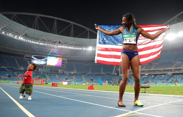 Nia Ali of USA celebrates with her son Titus in front of a sparse crowd in Rio