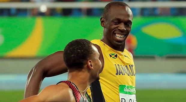 Usain Bolt of Jamaica and Andre de Grasse of Canada smile as they compete. Reuters/Gonzalo Fuentes