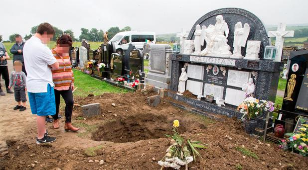 Maughan family members beside the desecrated grave of Michael at Boharnabreena Cemetry today. Photo: Colin O'Riordan