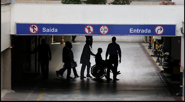 Pat Hickey, in wheelchair, is escorted by police to a waiting car at the Hospital Samaritano in Rio de Janeiro. Photo: Steve Humphreys
