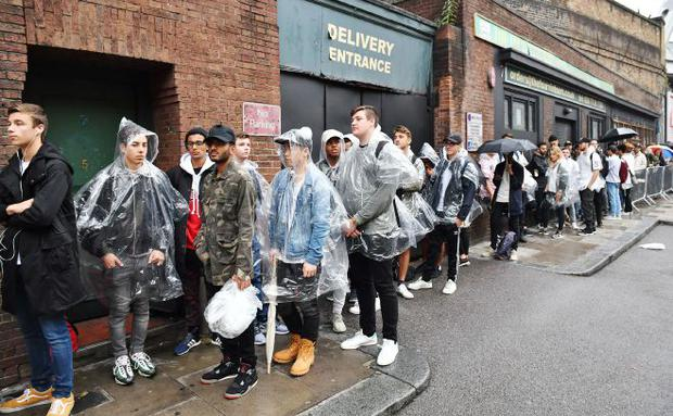 Fans queue in the rain ahead of the opening of a pop-up shop dedicated to Kanye West's album The Life of Pablo in Shoreditch, east London.