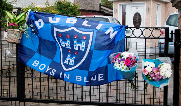 A Dublin flag and floral tributes hang on the gate outside the Dublin home of Trevor O'Neill