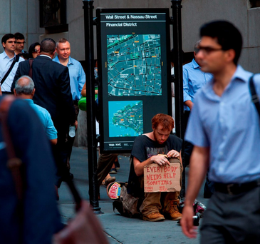 Pedestrians walk past a man sitting on the sidewalk holding a sign on Wall Street near the New York Stock Exchange (NYSE) in New York Photo: Bloomberg