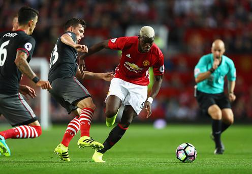 MANCHESTER, ENGLAND - AUGUST 19: Paul Pogba of Manchester United skips a challenge by Pierre-Emile Hojbjerg of Southampton during the Premier League match between Manchester United and Southampton at Old Trafford on August 19, 2016 in Manchester, England. (Photo by Michael Steele/Getty Images)