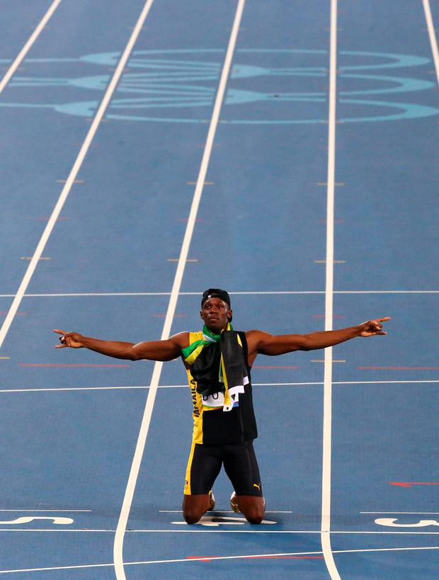 Usain Bolt (JAM) of Jamaica celebrates after the team won the race REUTERS/David Gray