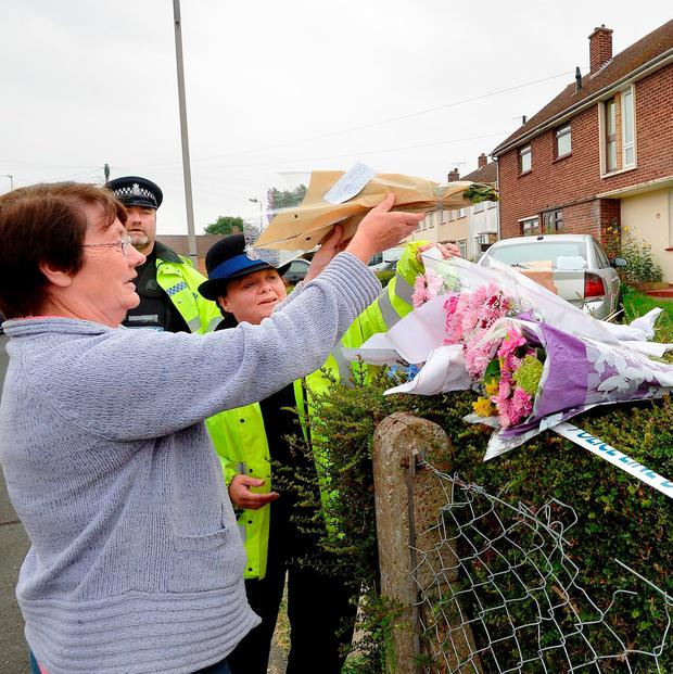 A woman places a bunch of flowers outside a property in Parker Way, Halstead, Essex where three year old Dexter Neal was bitten by a dog: John Stillwell/PA Wire