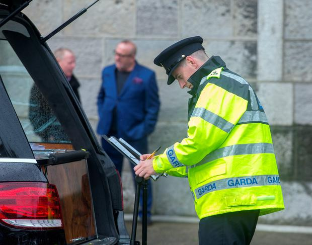 A Garda signs the book of condolence at the funeral of Ben Farrell, 'Batman Ben' at the Church of the Sacred Heart in Arbour Hill. Photo: Tony Gavin