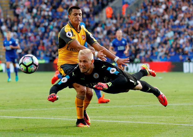 Leicester City's Kasper Schmeichel heads clear of Arsenal's Alexis Sanchez