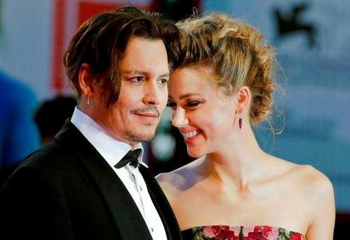 HAPPIER TIMES: Amber Heard and Johnny Depp at the Venice Film Festival last September. She has donated all of last week's $7m divorce settlement to charity. Photo: AP Photo/Andrew Medichini