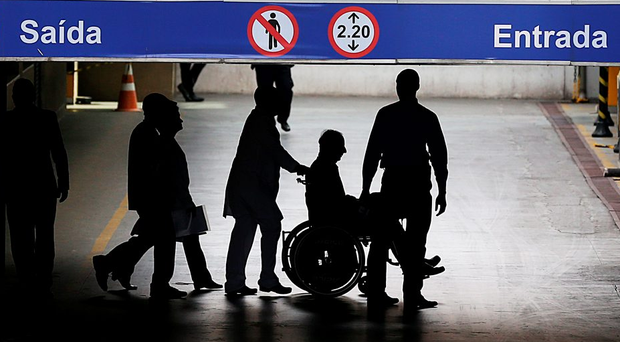 Controversey: Pat Hickey is escorted by police in a wheelchair at the Hospital Samaritano in Rio de Janeiro. Photo: Steve Humphreys