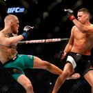 Conor McGregor kicks Nate Diaz during their welterweight rematch at the UFC 202