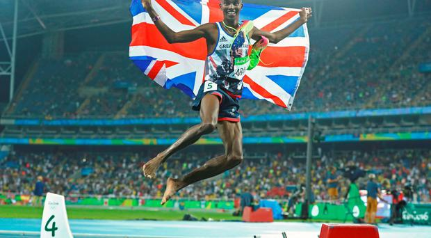 Mo Farah of Britain poses after winning the gold
