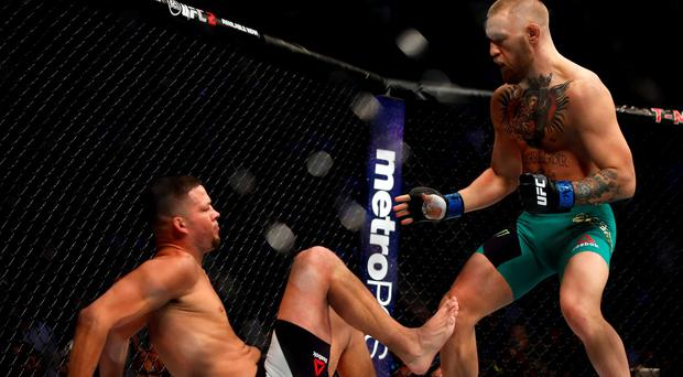 Conor McGregor stands over Nate Diaz during their welterweight mixed martial arts bout at UFC 202