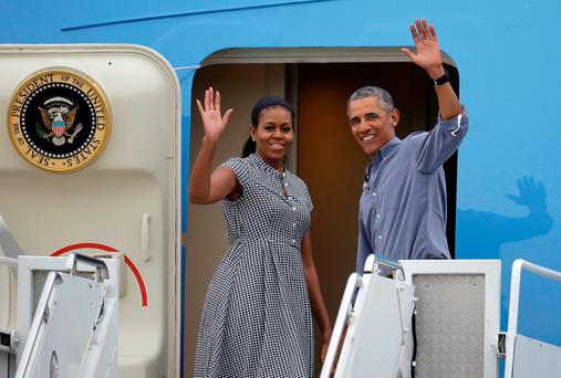 President Barack Obama, right, and first lady Michelle Obama wave as they board Air Force One at the Cape Cod Coast Guard Station in Bourne, Mass., Sunday, Aug. 21, 2016. President Obama and the first family are returning to Washington D.C. following their vacation on the island of Martha's Vineyard in Massachusetts. (AP Photo/Steven Senne)