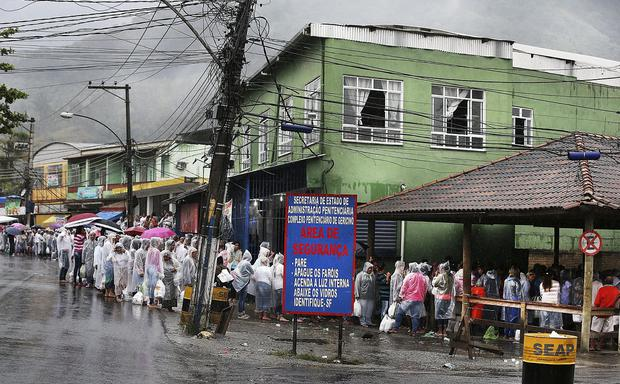 Women queue with food parcels in the pouring rain for hours to visit relatives at the notorious Bangu Prison in Rio de Janeiros where Pat Hickey and Kevin Mallon are reportedly sharing a cell. Pic Steve Humphreys