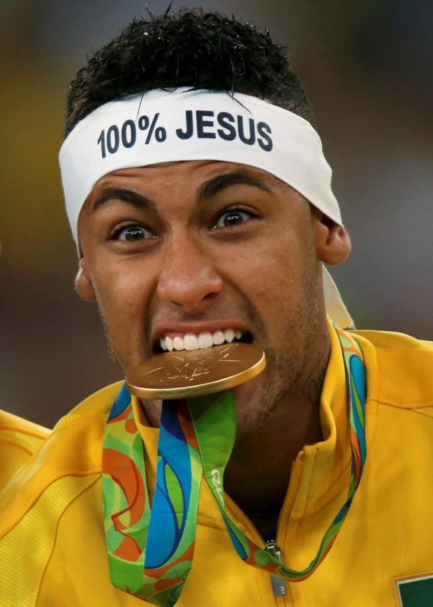 Brazil's Neymar bites his medal. Photo: Ueslei Marcelino/Reuters