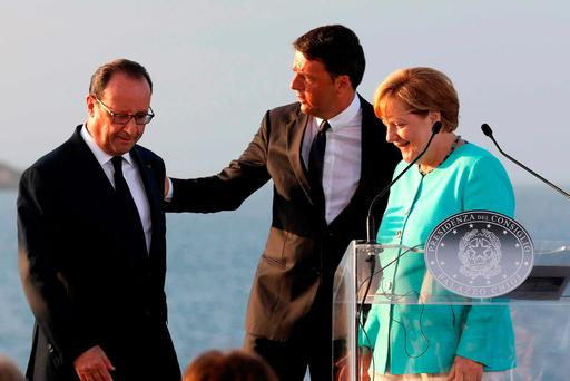 Italian Premier Matteo Renzi, center, stands between French President Francois Hollande, left, and German Chancellor Angela Merkel, on the deck of the Italian aircraft carrier Garibaldi off Ventotene island's shores. Photo: Cesare Abbate/ANSA via AP