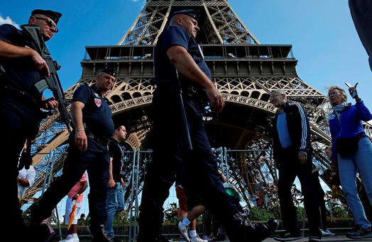 French police patrol as tourists gather at the Eiffel Tower in Paris, France. Photo: Pascal Rossignol. Photo: Reuters