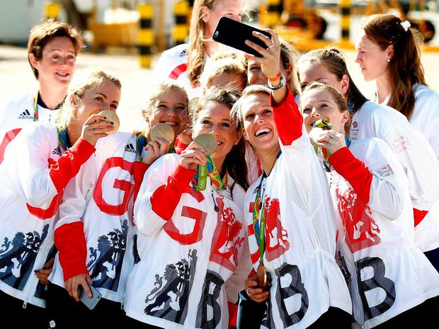 The UK women's hockey team celebrate their gold medals on their return to Heathrow. Photo: Reuters