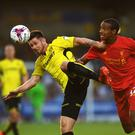 Calum Butcher of Burton Albion is challenged by Joel Matip of Liverpool (Photo by Gareth Copley/Getty Images)