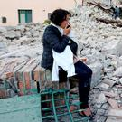 A woman sits amongst rubble following a quake in Amatrice, central Italy, August 24, 2016. REUTERS/Remo Casilli