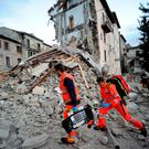 Rescuers search a crumbled building in Arcuata del Tronto, central Italy, where a 6.1 earthquake struck just after 3:30 a.m. (AP Photo/Sandro Perozzi)