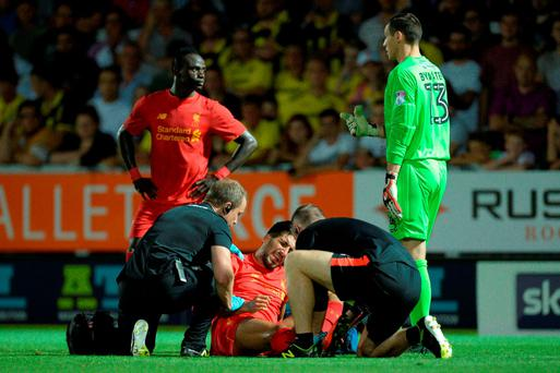 Liverpool's Emre Can receives attention on the field