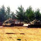 Turkish army tanks are stationed near the border with Syria, in Karkamis, Turkey (DHA via AP)