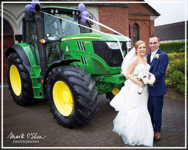James Donaghy pictured with his wife Stacey Burke in front of a John Deere tractor
