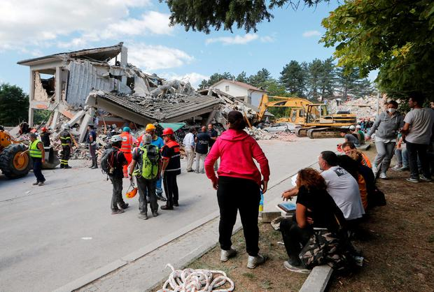 People and rescuers stand near collapsed buildings following an earthquake in Amatrice, central Italy, August 24, 2016. REUTERS/Ciro De Luca