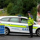 Garda at the scene of the crash, inset, Daniel Roche