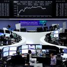 Traders work at their desks in front of the German share price index, DAX board, at the stock exchange in Frankfurt. Photo: Reuters