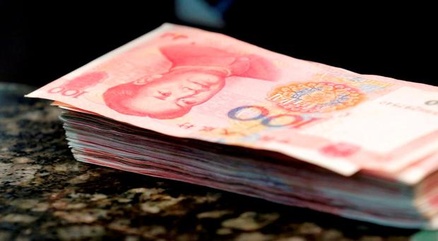 Chinese 100 yuan banknotes are seen on a counter of a branch of a commercial bank in Beijing, China