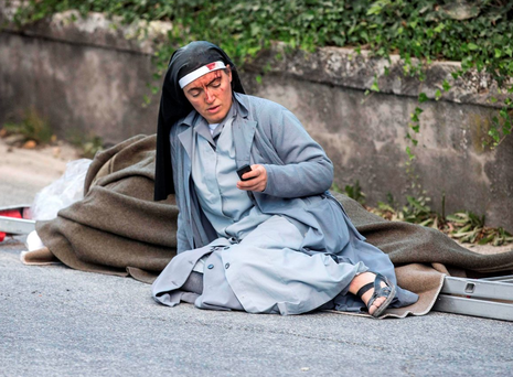 A nun checks her mobile phone as she lies near a makeshift stretcher following an earthquake in Amatrice, central Italy Photo: Massimo Percossi/ANSA via AP