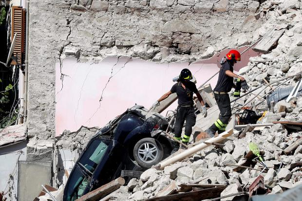 Rescuers make their way through destroyed houses following Wednesday's earthquake in Pescara Del Tronto, Italy, Thursday, Aug. 25, 2016