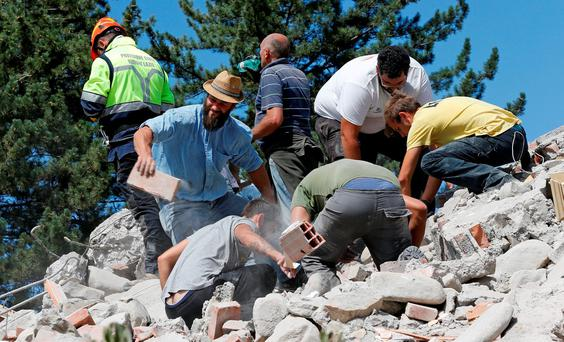 Rescuers work on a collapsed building following an earthquake in Amatrice, central Italy, August 24, 2016. REUTERS/Ciro De Luca