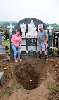 Distraught Helen Maughan and her husband Joe beside the desecrated grave of their son Bobby Maughan at Boharnabreena Cemetry. Photo: Colin O'Riordan
