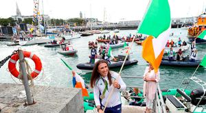 Olympic hero Annalise Murphy carries the Irish Tricolour after arriving via a flotilla in Dún Laoghaire Harbour Photo: MAXWELLPHOTOGRAPHY.IE