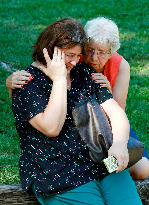Jonell Payton, right, comforts Lisa Dew, outside the Durant, Miss., home of two slain Catholic nuns, Thursday, Aug. 25, 2016