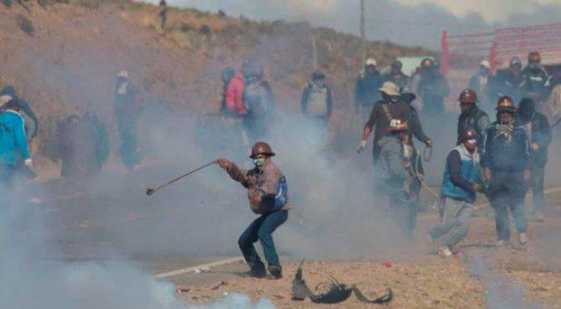 Independent miners clash with the police as they run from clouds of tear gas during protests in Panduro, Bolivia Credit: AP