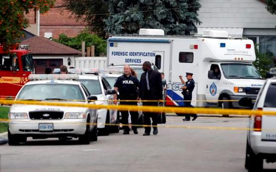 Police stand as a Forensic Identification Services truck arrives at a crime scene