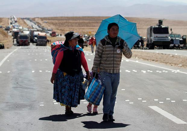 Passengers from a bus walk on a blocked main highway by independent miners protesting against Bolivia's President Evo Morales' government policies, in Panduro south of La Paz, Bolivia, August 25, 2016. REUTERS/David Mercado