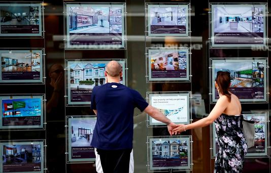 A couple view properties for sale in an estate agents window in London. Photo: REUTERS/Peter Nicholls