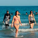 A Tunisian women wearing a burkini walking in the water at Ghar El Melh beach near Bizerte, north-east of the capital Tunis. Photo: Getty